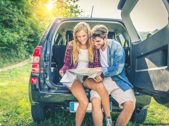 Young Couple Sitting in Back of a Car With a Map to the Cascade Loop Scenic Highway
