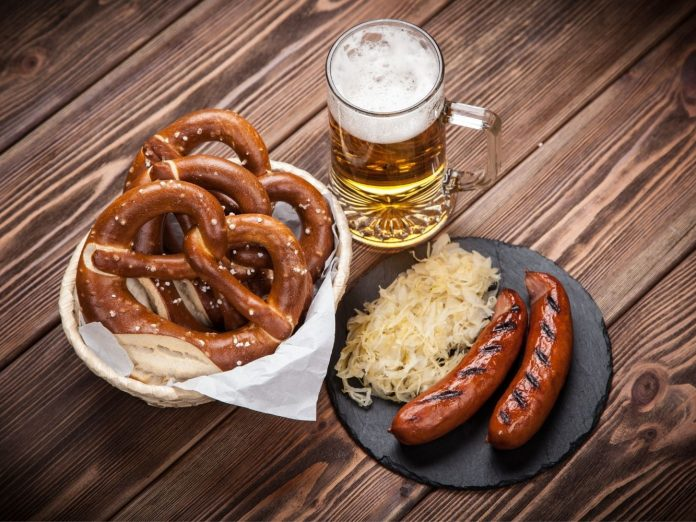 Pretzels, sausage, and beer on a table.