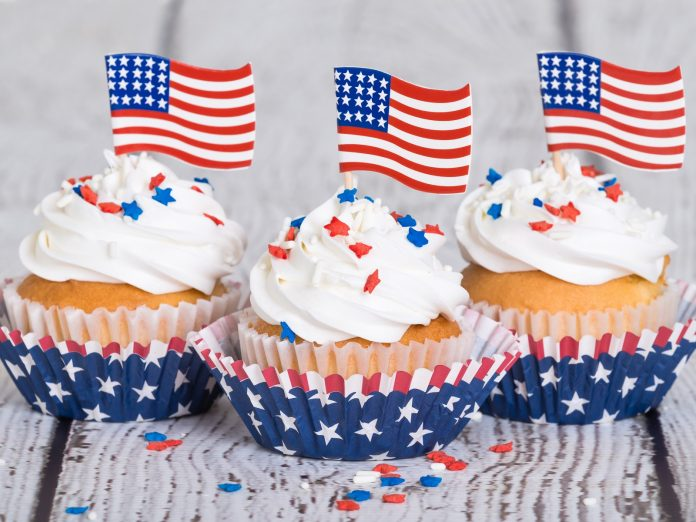 Patriotic cupcakes with sprinkles and American flags on vintage background