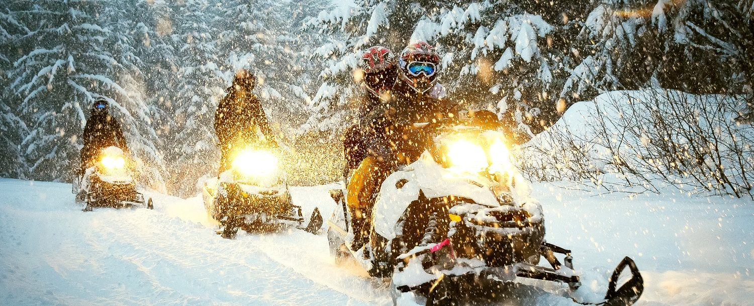 Visitors Enjoying a Snowmobile in Leavenworth During a Gentle Snowfall