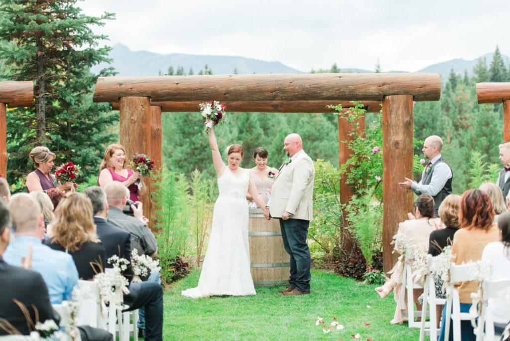 bride raising bouquet in the air