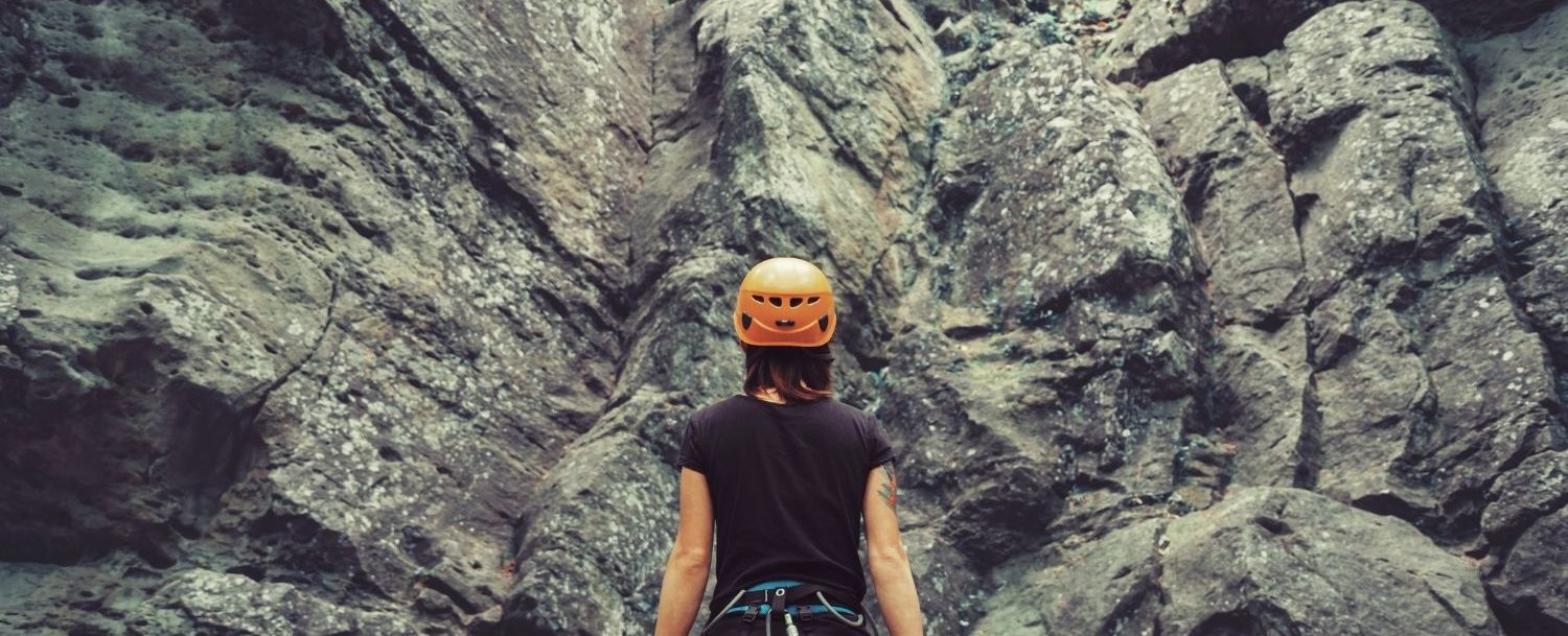 Woman in gear standing in front of a rock climbing wall.