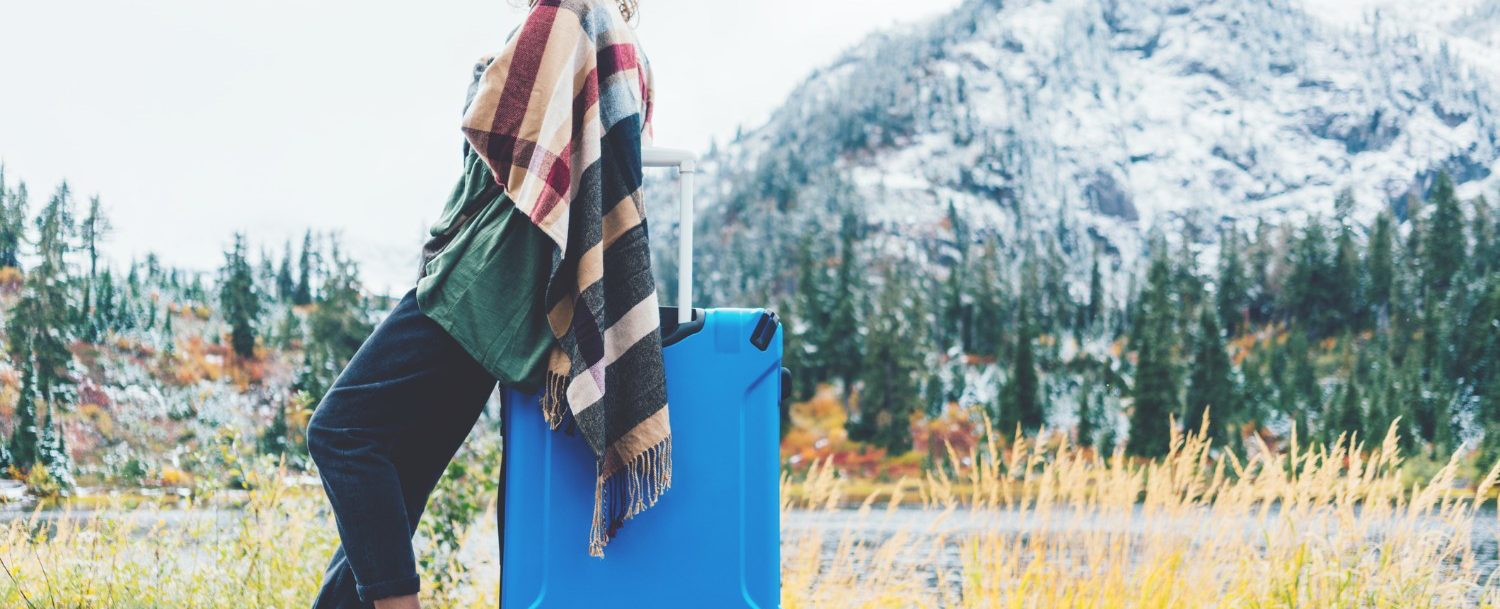 Traveling woman wearing poncho and hat sitting on her bright blue suitcase near stunning mountain wilderness. Wanderlust and boho style (Traveling woman wearing poncho and hat sitting on her bright blue suitcase near stunning mountain wilderness. Wand