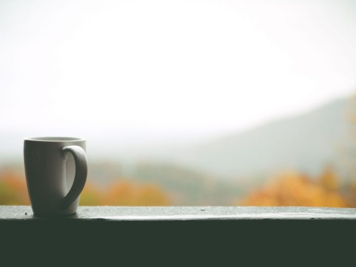 Coffee cup with mountain background.